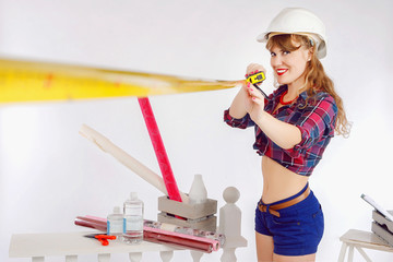 The girl in the style of Pin Up. Girl builder in the style of pin up. The girl measures the distance with a tape measure.