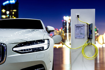 EV Car or Electric car at charging station with the power cable supply plugged in on blurred Night cityscape background.