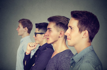 Row of young men posing on gray