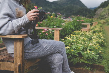 young woman sit on wood bench in park. girl check setting & photo in camera in garden.