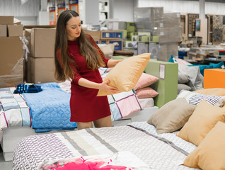 Customer woman chooses bed linen and bed in the supermarket mall store. She is taking pillow
