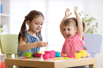 Children playing with plastic tableware
