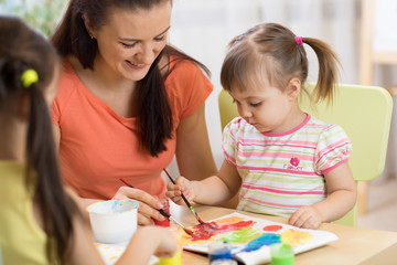 Teacher and little girls are painting in daycare center. Woman and children have a fun pastime.