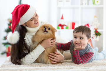 Happy little kid boy, mother and dog at Christmas