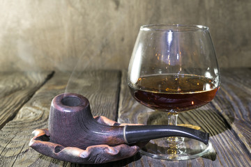 A Smoking pipe in the ashtray and a glass of cognac on oak textured table.