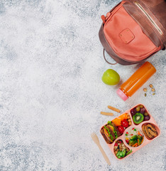 Open lunch box with healthy food on the grey background near backpack