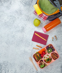 Open lunch box with healthy food on the grey background near school backpack with copy space