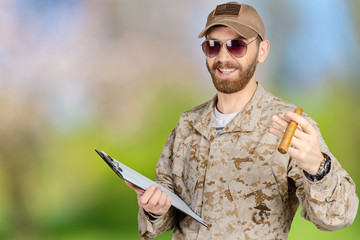 Portrait of young army soldier with a clipboard