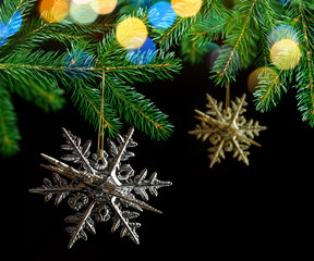 Christmas decoration in the shape snowflake hanging on fir branch on black background.
