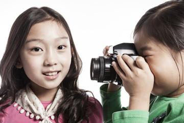girls(kids) hand hold a camera isolated on the white background.