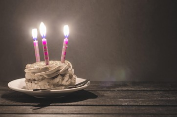 Chocolate cake with cream and  three burning candles on a dark background