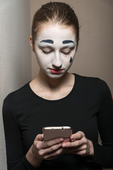 The girl in the image of mime with the phone