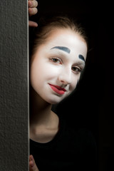 The girl wth makeup of mime hiding behind the wall