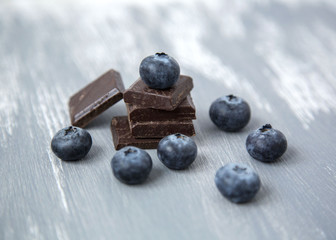 Close up Dark Chocolate Stack and Fresh Organic Blueberries on Wooden Background Natural Light Selective Focus