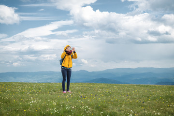 Girl taking photos with cellphone in nature.