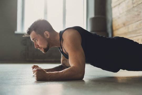 Young man fitness workout, elbow plank
