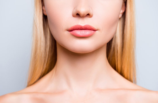 Close up cropped photo of attractive woman's lips without lipstick and after having shape correction, she has expression wrinkles. She is isolated on grey background