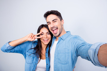 Sweet, caucasian, cheerful lovely couple in casual outfit - man making self portrait, woman showing peace symbol near her eye, standing over grey background