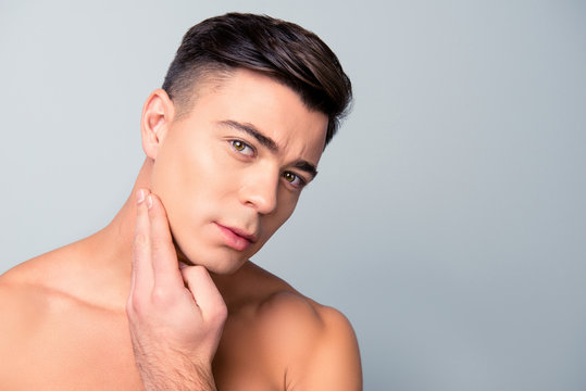 Close up portrait of satisfied confident handsome guy touching with shaved flawless clean soft skin after morning shaving, isolated on grey background, copy-space