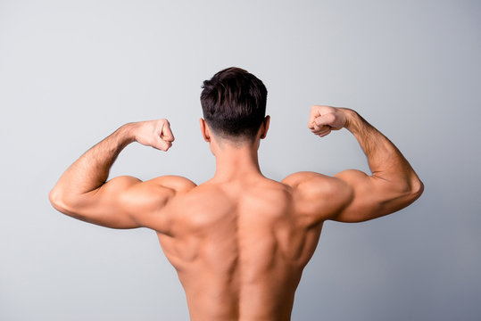 I am in favour of healthy lifestyle, sport, diet and nutrition! Back view photo of handsome confident man showing his muscular arms, isolated on grey background