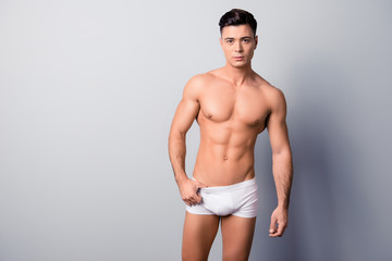 Portrait of handsome sexy virile muscular with modern hairstyle gut, he is posing in white underwear, isolated on grey background, copyspace