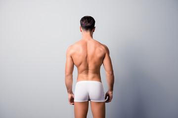 Back view photo of handsome confident guy with strong back and shoulders, wearing white underpants, isolated on grey background, copyspace