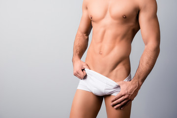Cropped photo of perfect man's body with flawless ans hairless skin, his muscular hands are taking off the underwear, isolated on grey background