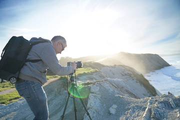 Photographer using tripod to take pictures of landscape