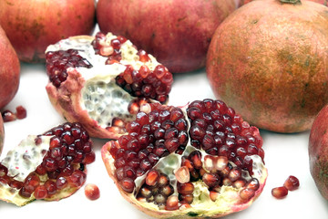 Whole and half pomegranates with ripe seeds on white background top view closeup