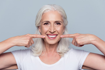 Concept of having strong healthy straight white teeth at old age. Close up portrait of happy with...