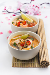 Traditional Tom Yum soup with blooming sakura branch on white stone table