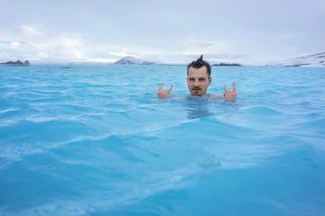 Guy relaxing in geothermal pool outdoors