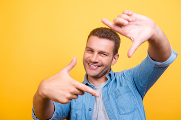 Closeup of young, happy man with stubble making diagonal frame in front of face with fingers, over yellow background