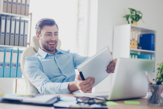 Cool game! Close up portrait of happy careless excited cheerful delightful full of fun young with bristle and toothy smile accountant, he is playing video game on his digital tablet