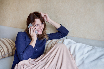Attractive young woman talking on mobile phone and smiling at home