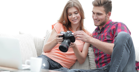 happy young couple checks photos on photos the camera
