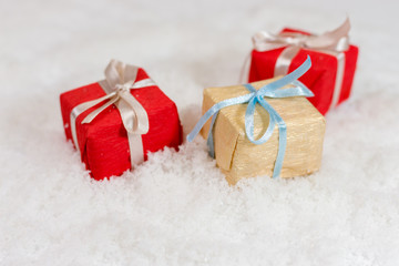 three small Christmas presents on snow, shallow depth of sceene