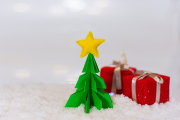 miniature paper pine tree figure with felted star on the top and red gift boxes, selective focus