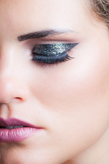 beauty closeup of woman face with glittering eyeshadow