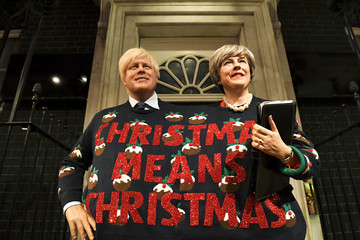 Madame Tussauds' wax figures of Britain's Prime Minister Theresa May and Foreign Secretary Boris Johnson wear one Christmas themed jumper between them and hold a sign, in London