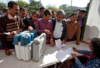 Polling officials wait to receive VVPAT machines and EVM at a distribution centre ahead of the final phase of voting in Gujarat state assembly election in Ahmedabad
