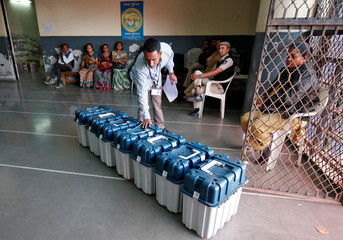 A polling official checks serial numbers on VVPAT machines at a distribution centre ahead of the final phase of voting in Gujarat state assembly election in Ahmedabad