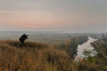 the photographer is shooting the autumn landscape with the sunrise by the river
