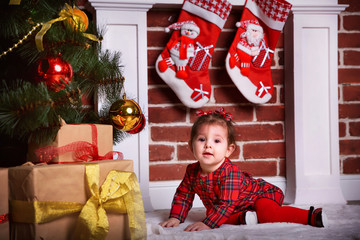 smart girl in a beautiful red dress sitting near the fireplace and Christmas tree