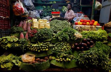 A vegetables vendor waits for customers at a market in Kolkata