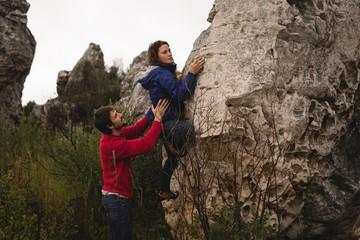 Man assisting woman in rock climbing