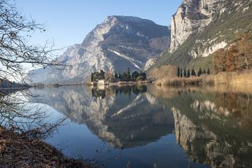lago con riflesso di un castello e rami in primo piano
