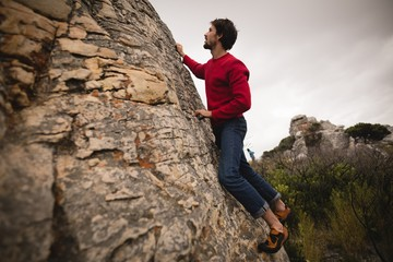 Determined man climbing cliff