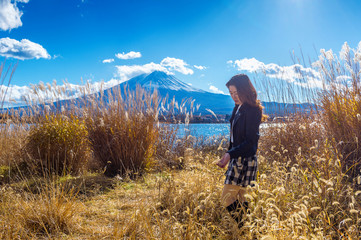 Wall Mural - Beautiful girl standing at kawaguchiko lake with view of Fuji mountain, Autumn in Japan.