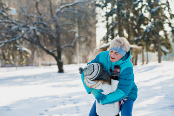 Active atractive grandmother in sporty jacket and her granddaughter play together in winter city park